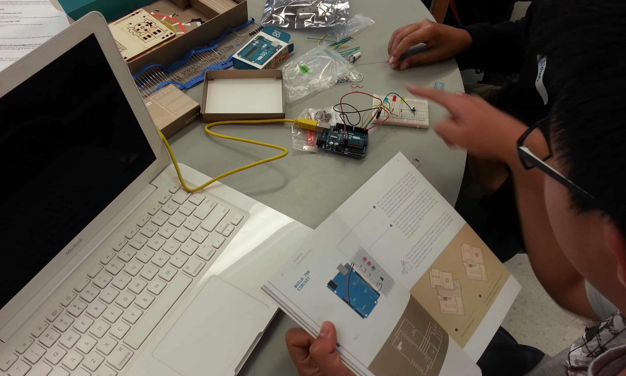 Students using resources to learn Arduino.